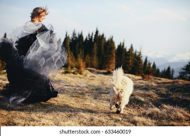 Woman runds in magnificent dress with dog on hill