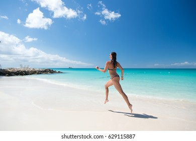 woman runing with beautiful body in swimsuit running in ocean water sunny day at tropicl beach, sport and wellness concept
