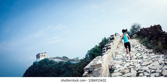 woman runner athlete cross country running on chinese great wall.