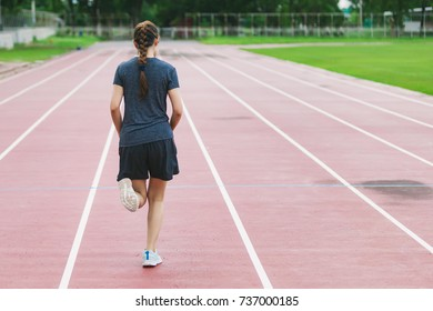 woman runner athlete feet running on road on Running Track