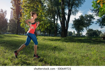Woman runner in a city park. Copy space.