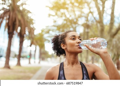Woman runner drinking water from a bottle during workout. Female athlete taking a break from her workout.