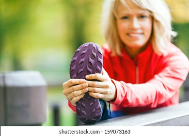 Woman runner exercising and stretching, autumn outdoors. Beauty blonde girl after workout relaxing, sport and fitness. Walking running exercise in nature