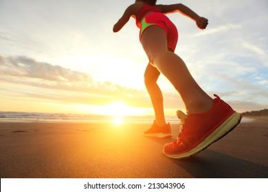 Woman Runner feet running on the beach at sunrise closeup on shoe. woman fitness sunrise jog workout wellness concept. asian
