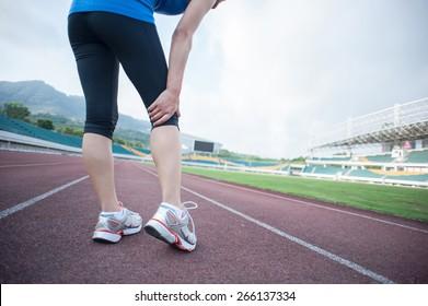 woman runner hold her injured leg on track