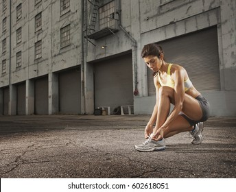A woman runner leaning down and tying her running shoes laces