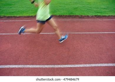 woman runner legs  running on red track in stadium