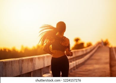 The woman with runner on the street be running for exercise.