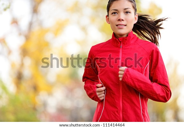 秋の森を走る女性ランナー。秋色のジョギングをする若い混血児。