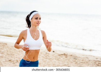 Woman runner running on the beach listening to music on smartphone using earphones. Female fitness girl jogging on path in amazing fall foliage landscape nature outside.