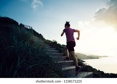 Woman runner running up on seaside mountain stairs