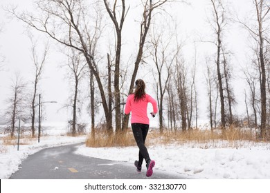 Woman runner running in winter snow - active lifestyle. Female athlete from the back jogging training her cardio on city park path outside in cold weather wearing leggings and coat.