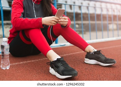 Woman runner in sportswear sitting on running track on stadium after training. Rest after training concept
