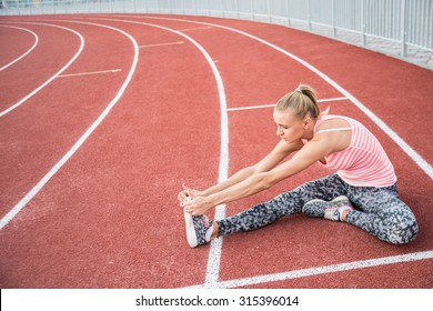 Woman runner stretching before workout - outdoor shot. Sport girl doing exercise in the stadium. teenage female sitting on the treadmill. Sporty racetrack texture with white round lines