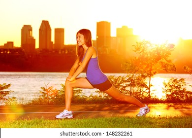 Woman runner stretching legs after running training in sunshine at sunset. Fit female jogger athlete training outside in Montreal, Canada, Quebec.