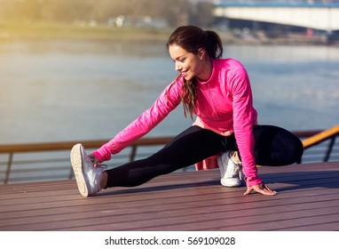 Woman runner stretching legs before run. Beautiful smiling young athlete woman working out. Fitness concept