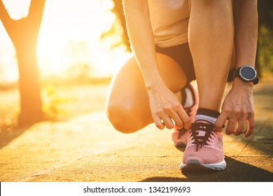 Woman runner tighting running shoes before run for exercise in the evening. Woman runner checking choes in order to get ready to run.