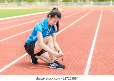 woman runner tying running shoe laces.