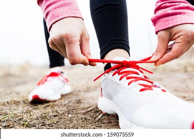 Woman runner tying sport shoes. Walking or running legs, autumn adventure and exercising outdoors. Motivation and inspiration fitness concept outside.