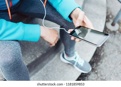 Woman runner using mobile phone on the street
