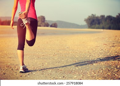 woman runner warm up before taking a jogging on beach
