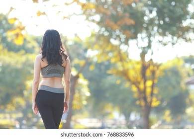 Woman runner warming up before running at park nature background