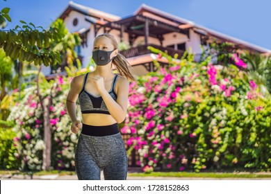 Woman runner wearing medical mask. Running in the park. Coronavirus pandemic Covid-19. Sport, Active life in quarantine surgical sterilizing face mask protection. Outdoor run on athletics track in