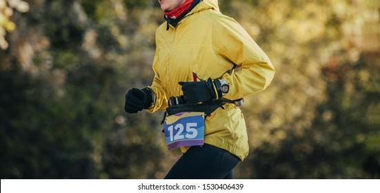 woman runner in yellow jacket run fall marathon