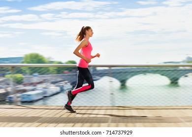 Woman running across bridge during cardio exercise