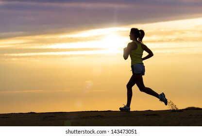 Woman running alone at beautiful sunset in the beach. Summer sport and freedom concept. Athlete training  on dusk.