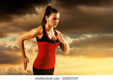Woman running alone at beautiful sunset. Sport and freedom concept. Woman athlete training on dusk.