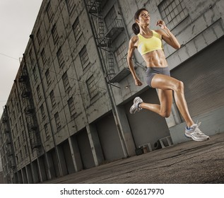 A woman running along an urban road, legs high and arms pumping