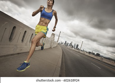 A woman running along an urban road pumping her arms and stretching her legs