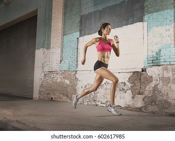 A woman running along an urban street past buildings with peeling paint and a metal shutter