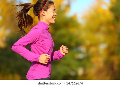 Woman running in autumn fall forest. Female runner training outdoor in profile. Healthy lifestyle image of young Asian woman jogging outside. Fit ethnic Asian Caucasian fitness model.
