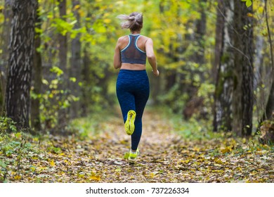 Woman running in the autumn park