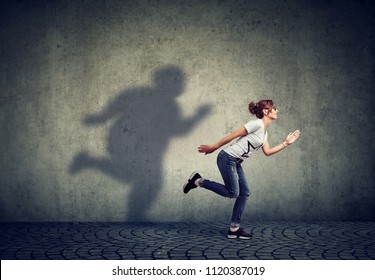 Woman running away from her fat shadow on the wall. Body weight control concept