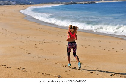 Woman running by the sea in morning, Portugal