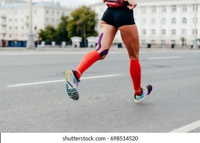 woman running city marathon in compressing socks and kinesiotape hamstring