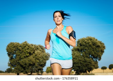Woman running cross trail in countryside on summer. Sweaty fit girl exercising.