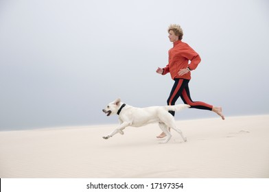 Woman running with dog on the dune