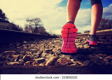 woman running down railroad tracks during the sunlight with retro instagram filter (shallow depth of field)