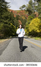 Woman running down the road with the fall trees behind her.