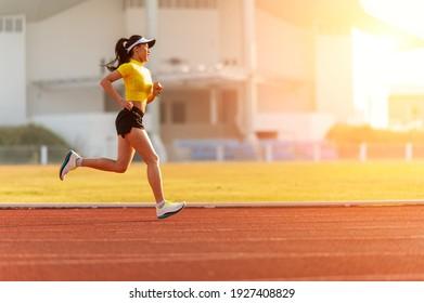 woman running during sunny morning on stadium track
