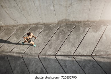 Woman running from her everyday problems at work and at home jogging her way into better life. Urban runner and sports concept.
