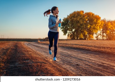 Woman running holding bottle of water in autumn field at sunset. Healthy lifestyle concept. Active sportive people