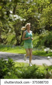 Woman running to keep & stay fit and healthy wearing green shorts and shirt Exercising outdoor