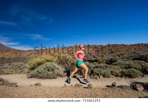 Woman running in mountains on sunny summer day. Beauty female runner jogging and exercising outdoors in nature, trail running training on rocky trail footpath on Tenerife, Canary Islands