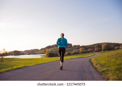 Woman running in nature in the middle of the road/ Girl doing sport