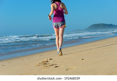Woman running on beach, beautiful girl runner jogging outdoors, training for marathon, exercising and fitness concept